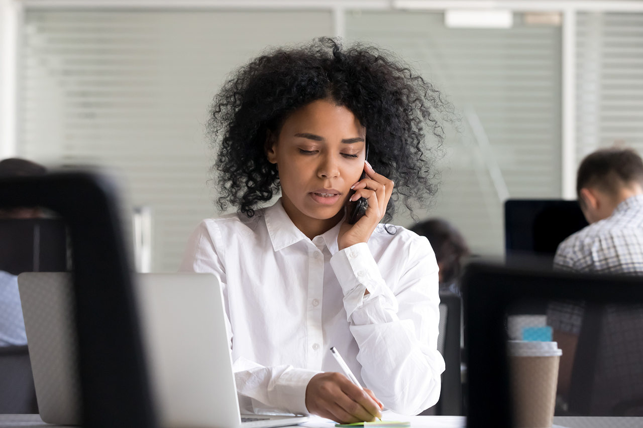 Woman making notes on sticker, clarifies information, talking on phone, registers complaint from client or customer, female employee consulting by mobile device at workplace